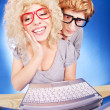 Funny guy is spying on girlfriend she is using laptop computer - Stock Photo