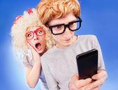 Chica es espiar a novio está usando un teléfono inteligente — Foto de Stock