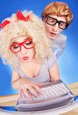Zabawny facet szpieguje dziewczyna, ona jest przy użyciu komputera przenośnego — Zdjęcie stockowe