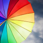 Rainbow umbrella on dramatic sky background — Stock Photo