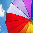 Stock Photo: Rainbow umbrella on blue sky background