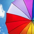 Rainbow umbrella on blue sky background — Stock Photo