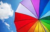 Rainbow umbrella on blue sky background — Stock Photo