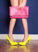 A woman showing off her yellow high heels and pink bag — Stok fotoğraf
