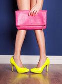 Una mujer mostrando sus tacones amarillos y rosa bolsa — Foto de Stock