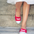 Girl wearing red sneakers leaning on the wall — Stok fotoğraf