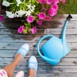 Woman with watering can and flowers on a patio deck — Stock Photo