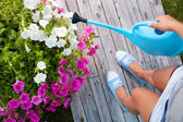 Woman watering flowers on a patio deck — Stock Photo