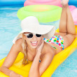 Young happy woman relaxing in a swimming pool — Stockfoto