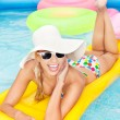 Young happy woman relaxing in a swimming pool — Stock Photo #29524247