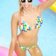 Young happy woman relaxing in a swimming pool — Stock Photo