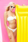 Beautiful young bikini girl with inflatable bed — Stock Photo