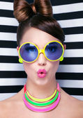 Surprised young woman wearing sunglasses — Stock Photo