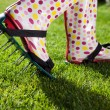 Woman wearing spiked lawn revitalizing aerating shoes — Stock Photo