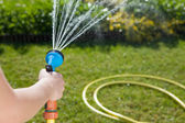 Woman's hand with garden hose — Stock Photo