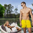 Young couple poolside — Stock Photo