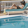 Young girl reading by the pool — Stock Photo