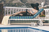 Pretty girl reading a book by the pool — Stock Photo