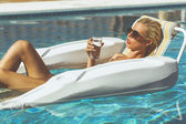 Blonde model chilling in a pool — Stock Photo
