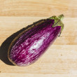 Eggplant on wooden chopping board — Stock Photo