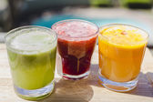 Yellow, green and red fruit and vegetable juices in tumbler glas — Stock Photo