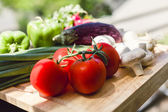 Fresh vegetables on wooden chopping board — Stock Photo