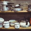 Shelves cluttered with pots and pans — Stock Photo #44855613