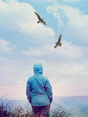 Woman looking at flying birds at sunrise — Stock Photo