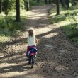 Stock Photo: Girl riding bicycle in forest