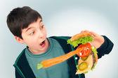 Carrot hitting hamburger held by boy — Stock Photo