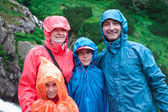 Family on mountain trail on a rainy day — Stock Photo