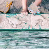 Kid creating animal forms in sandpit — Stockfoto
