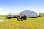 Tractor with big farm in the background — Stock Photo