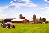 Traditional american red farm with tractor — Stock Photo