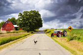 Country Road With Red Barn and Tractor On Side — Stock Photo