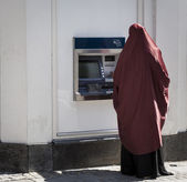 Muslim lady by cashpoint — Stock Photo