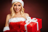 Beautiful girl with gift wearing santa claus clothes — Stock Photo