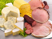 Ararangement with cheese, ham and sausage on table — Stock Photo