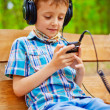 Stock Photo: Happy kid listening to music on stereo headphones