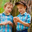 Stock Photo: Young stylish boys browse internet on mobile phone