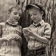 Stock Photo: Young stylish boys browse internet on mobile phone.
