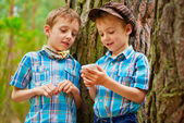 Young stylish boys browse the internet on mobile phone — Stock Photo