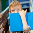 Постер, плакат: Young boy is hiding behind book
