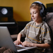 Young kid listening to music and browsing the internet — Stock Photo