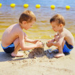 Two boys building sandcastle on beach — Stock Photo #27216595
