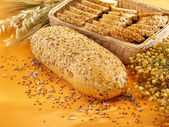 Multi-grain bread and wheat on table — Stock Photo