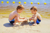 Two boys building sandcastle on the beach — Stock Photo