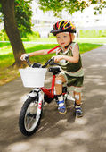 Young kid with injured knees is learning to ride a bike — Stock Photo
