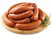 Sausages on round kitchen cutting board — Stock Photo