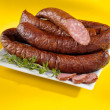 Baked sausages on a plate and yellow background. Tasty kielbasa — Stock Photo